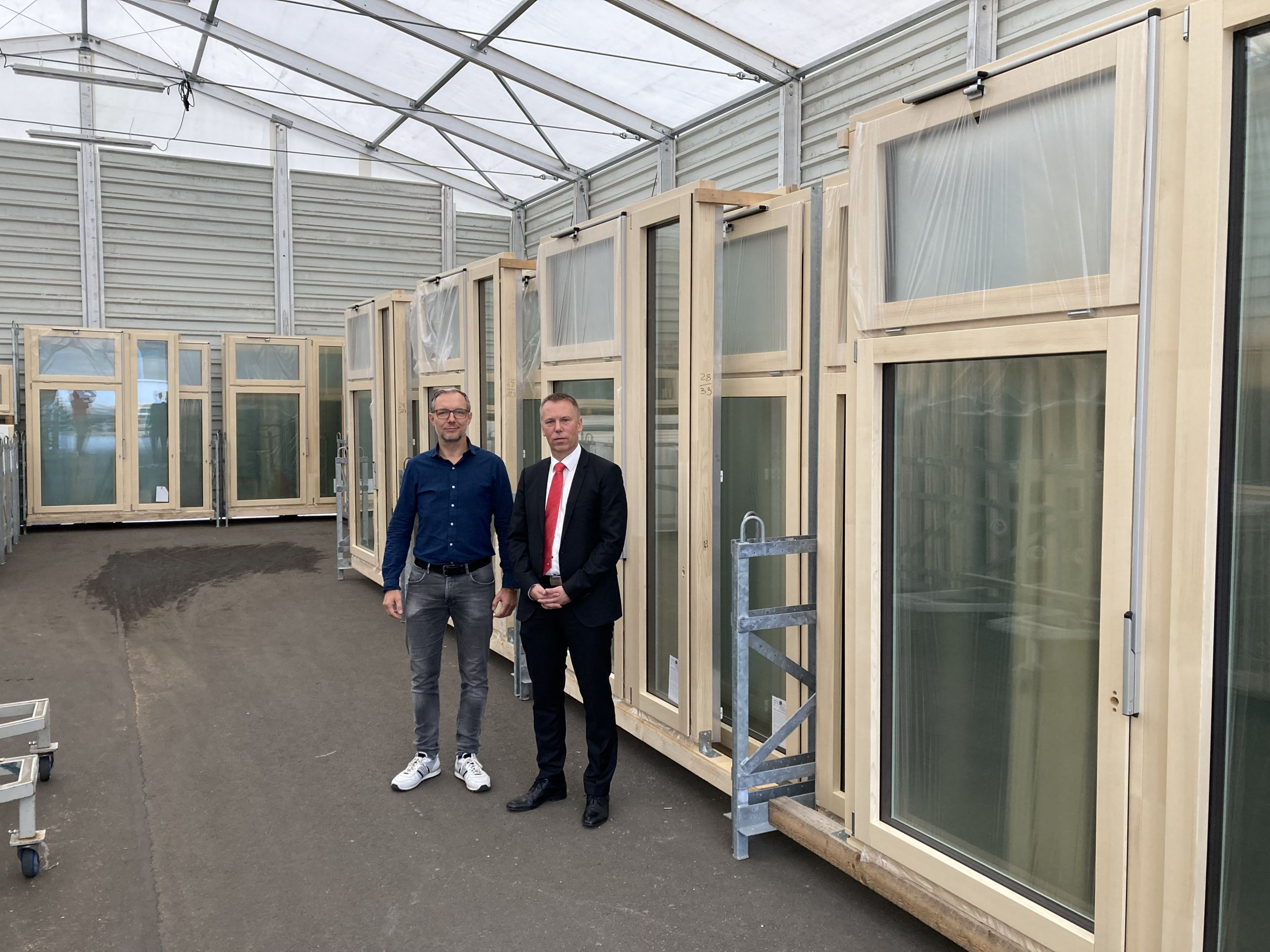 Ein Vertreter der KSK Stendal und der Geschäftsführer vom Unternehmen Innoline stehen vor vielen Glastüren